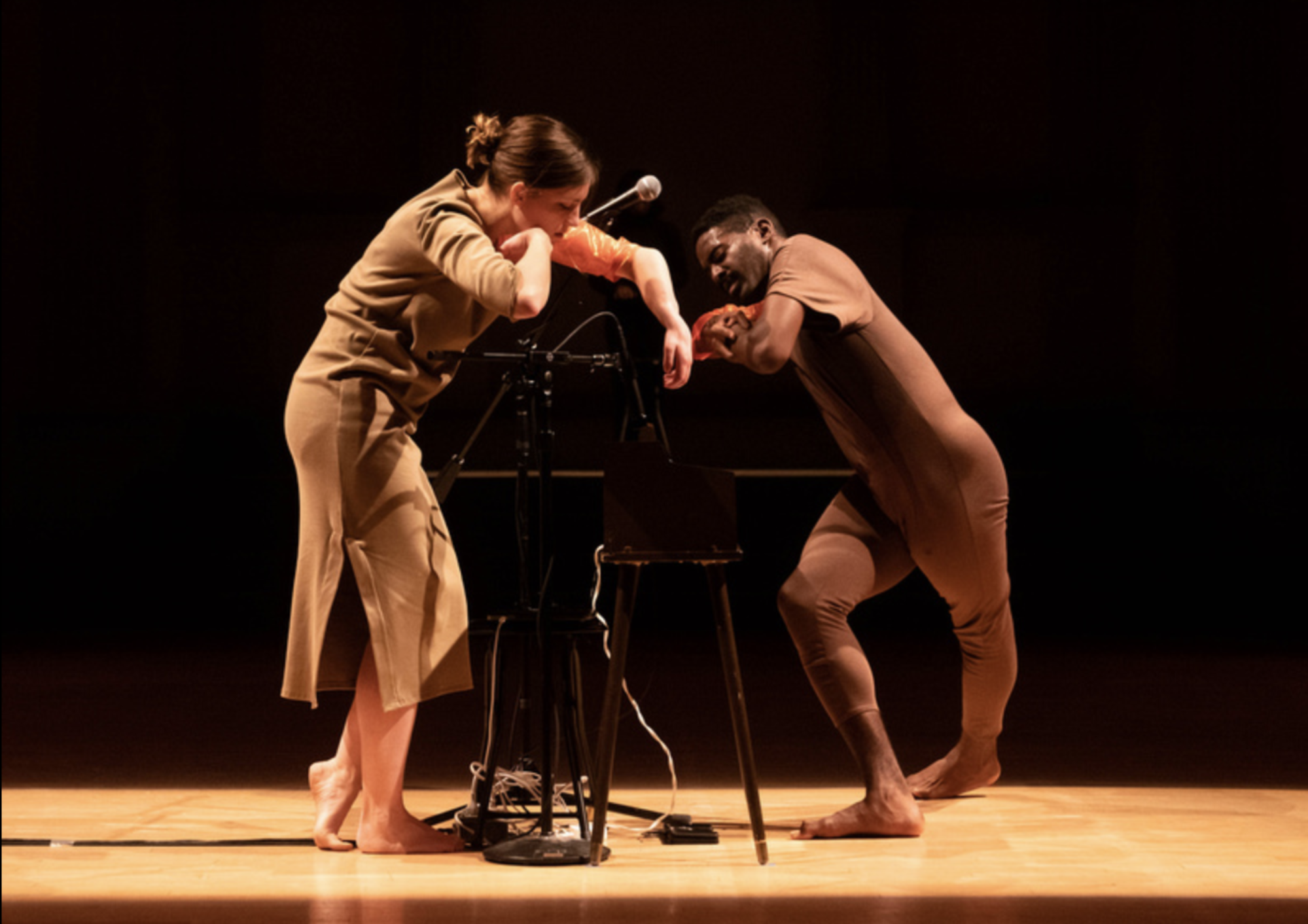 Jerron Herman and Molly performing on a brown vintage toy organ. Jerron is a Black man wearing a brown dance costume. Molly is a white woman wearing a tan dress costume with her hands reaching out to the organ, and microphone equipment in between.