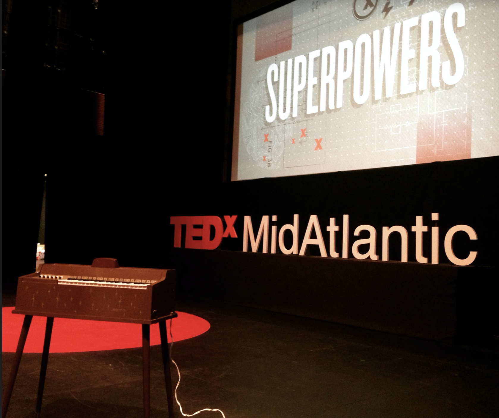 """A brown vintage toy organ with gold decal stands on the stage of TEDxMidAtlantic, with a red circle carpet behind it, the text """"TEDxMidAtlantic,"""" and image projected overheard with the word """"SUPERPOWERS."""""""