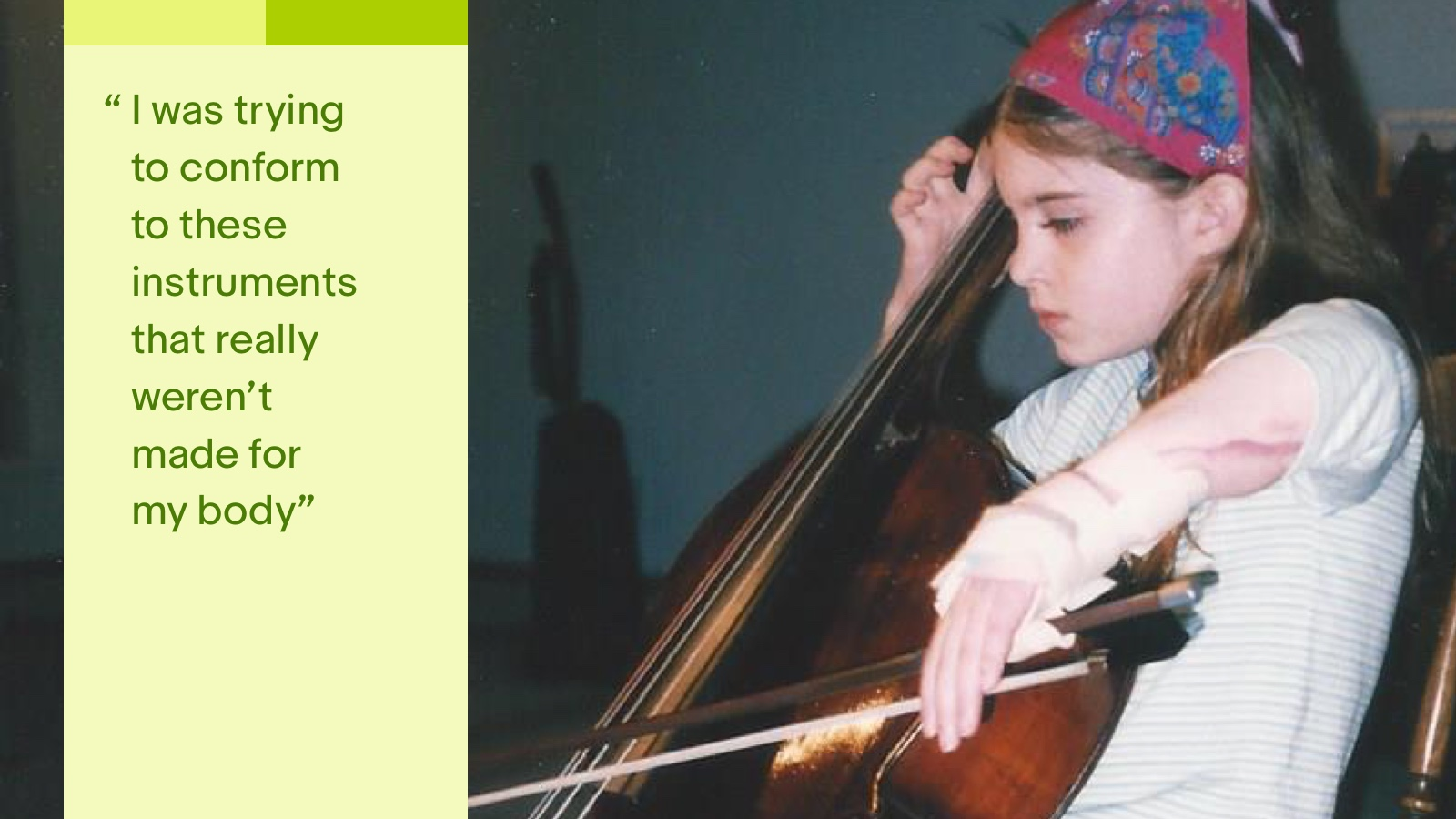 Molly, a white girl with short brown hair at eight years old, sitting in a brown wooden chair with a splint on her scarred left hand/arm which is attached to a cello bow. She is holding a brown cello, with her right hand on the cello fingerboard.