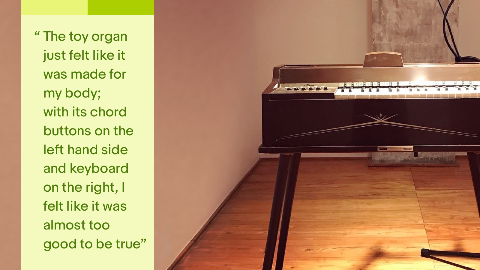 A brown vintage toy organ with gold decal stands on a brown wood floor in a hotel room in Shanghai, China.